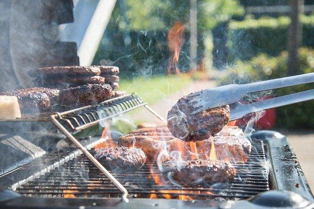 Dampfende Burgerpatties werden auf Gasgrill gegrillt