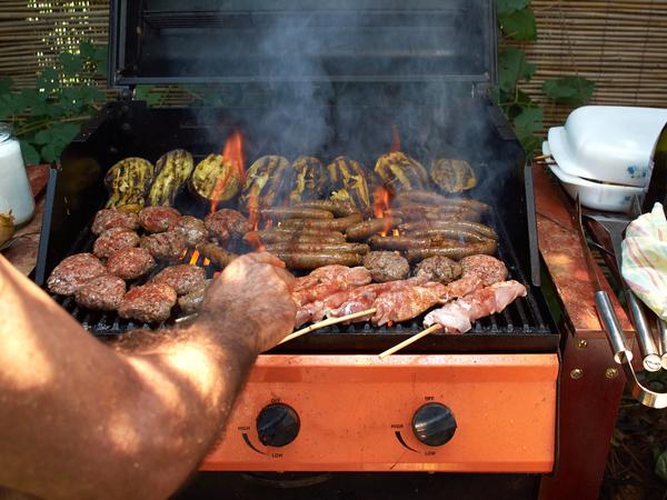 Verschiedene Fleischsorten auf orangenem Grill