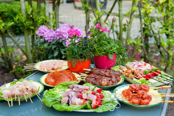 Bunte Grillspeisen auf einem Gartentisch